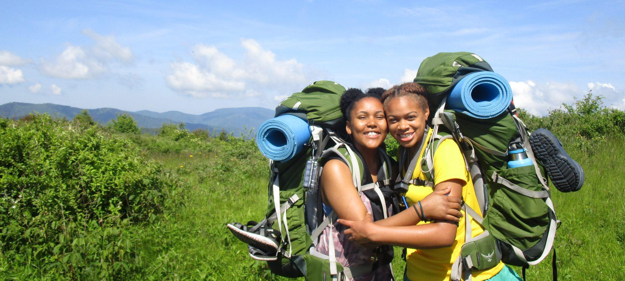 Two young women with backpacks smiling