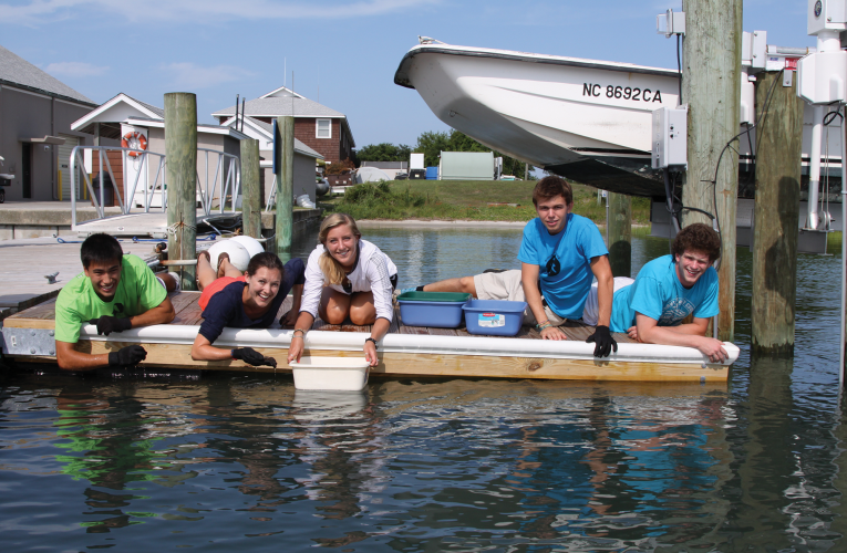 5 students on dock with gloves